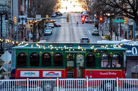 a trolley with holiday lights on a downtown Easton street