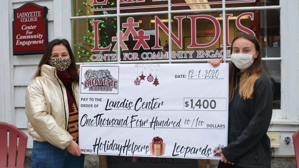 Two students hold a big check in front of the Landis Center