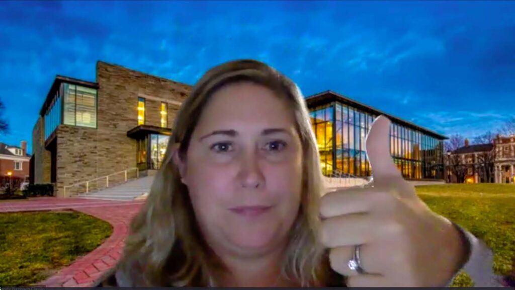 Sandy Furnbach Clavijo '03 with Skillman Library zoom backdrop gives her thumbs up