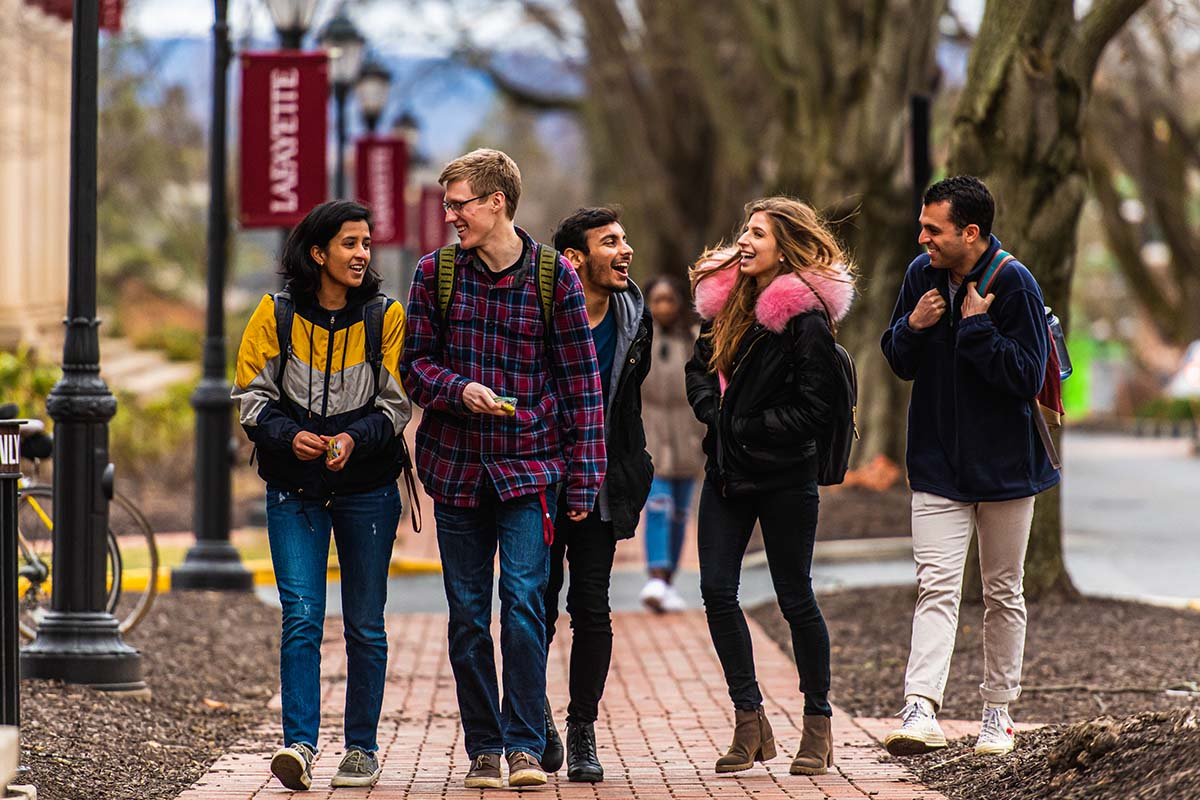 A group of 5 students talk while walking next to Markle Hall