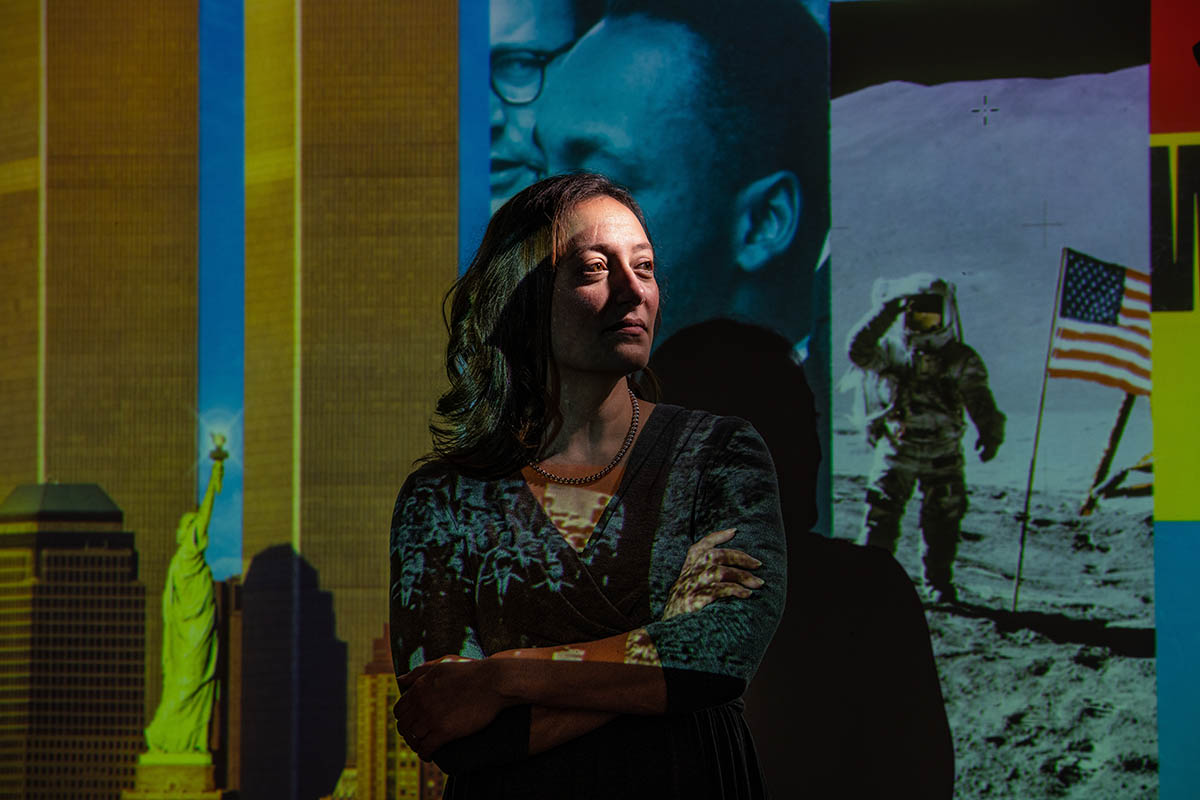 Jennifer Talarico stands with arms crossed in front of a screen depicting Martin Luther King Jr. and the first man on the moon with a US flag.