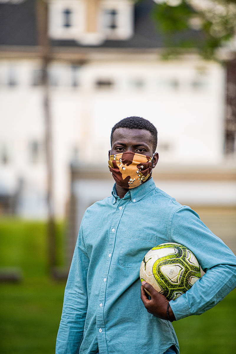 Basit Balogun '21, masked with a soccer ball in his left hand