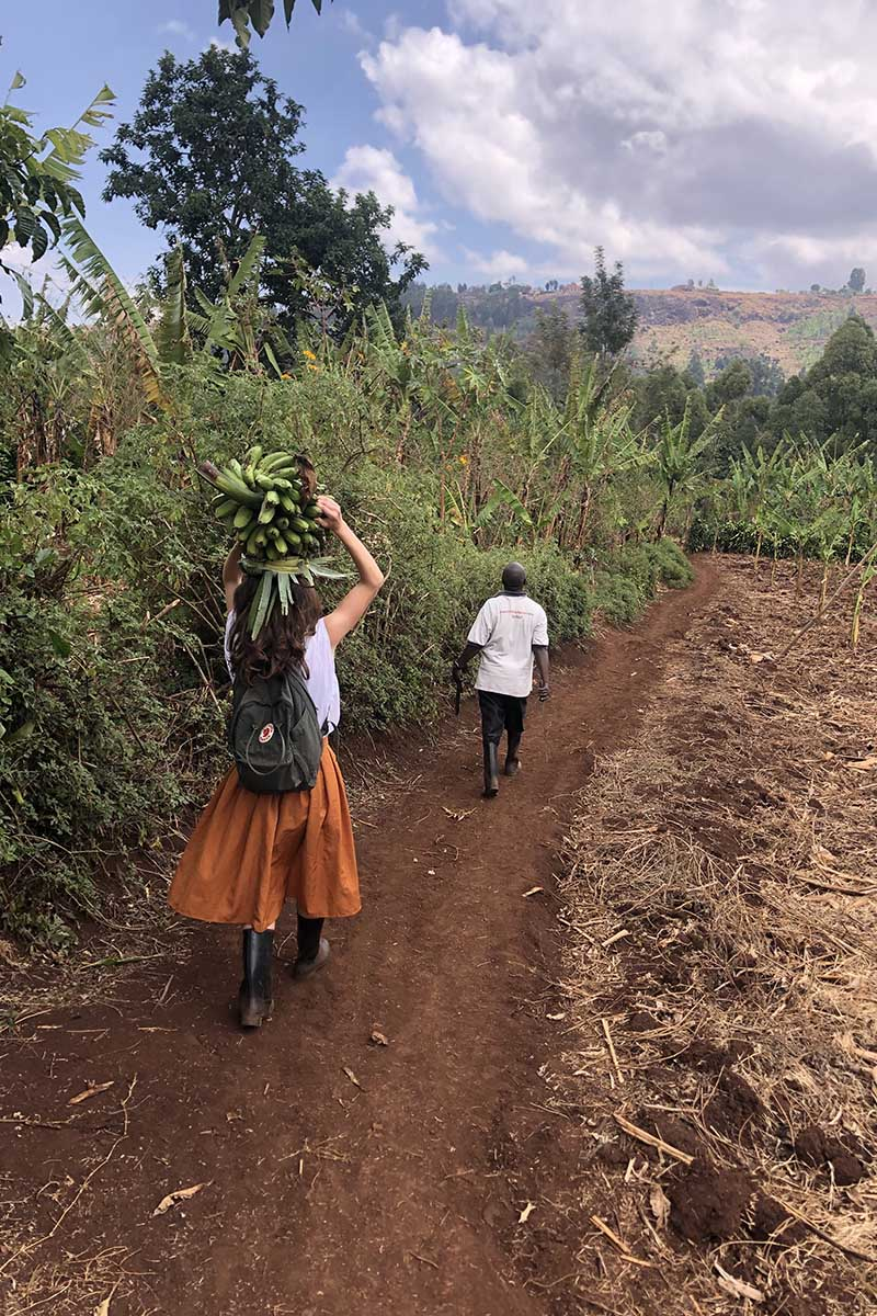 Victoria Puglia '21, facing away from the camera, carries bananas above her head; she is following a person on a dirt path, with greenery and blue skies surrounding her.