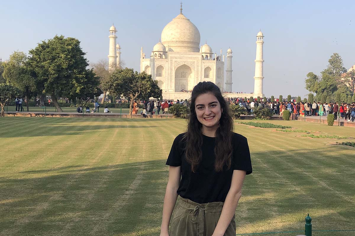Victoria Puglia '21, smiling, stands in front of the Taj Mahal in India.