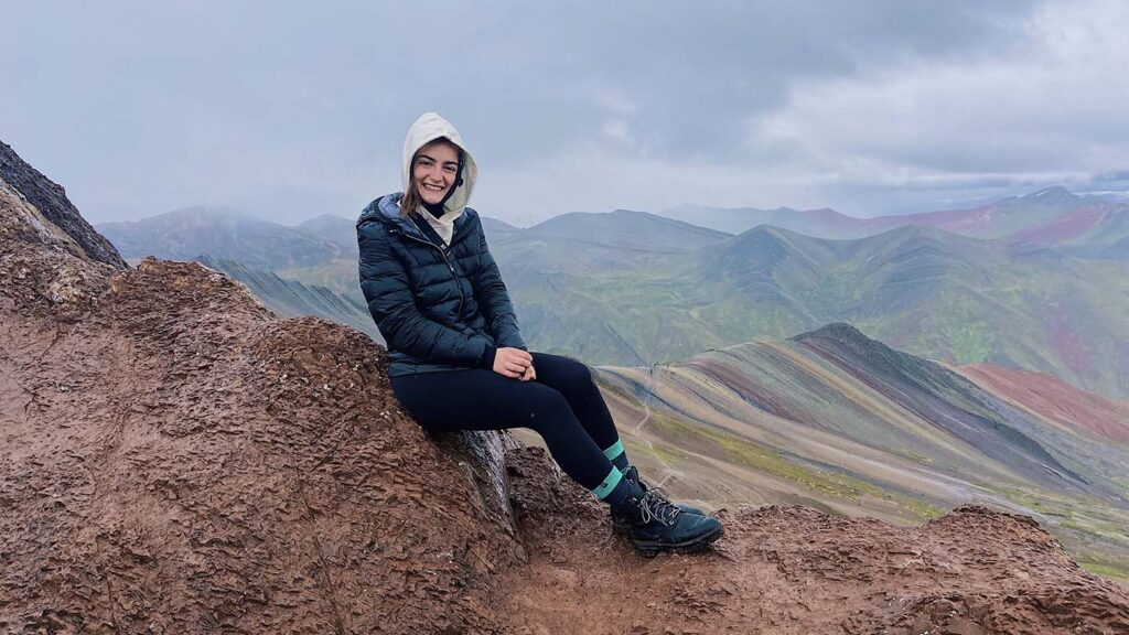 Victoria Puglia '21 sits on top of rocks with mountains in the background in Peru