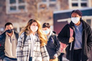 Masked students walk in front of Farinon College Center