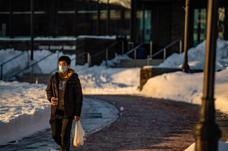 A masked student carries a container in front of Skillman Library