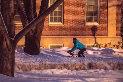 A masked bicyclist bikes past Markle Hall