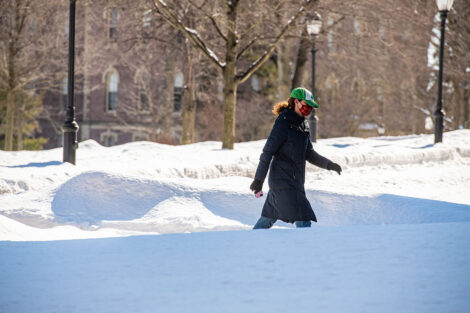 A masked person walks, surrounded by snow.
