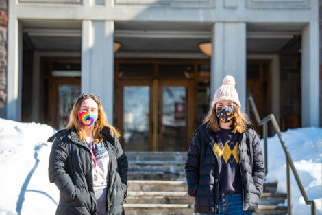 Two masked students stand in front of Farinon College Center