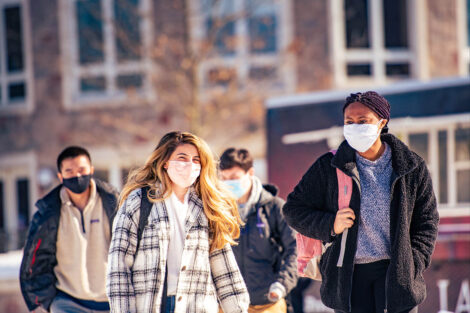 Four masked students walk.