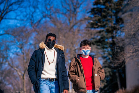 Two masked students walk.