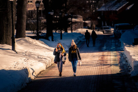 Two masked students walk up a brick sidewalk. Snow surrounds them.