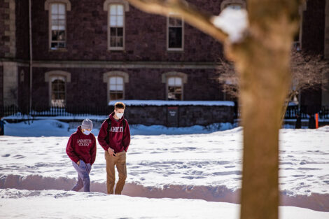 Two masked students in Lafayette sweatshirts walk past Hogg Hall. Snow surrounds them.