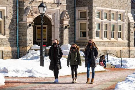Three masked students walk past Hogg Hall