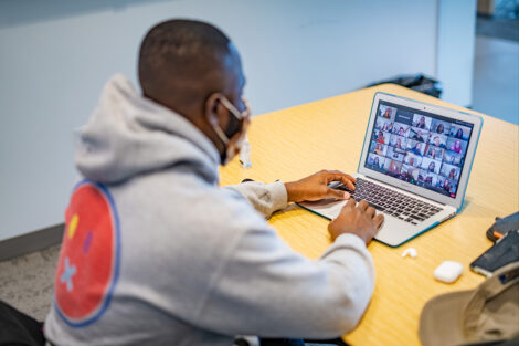 A masked student uses their laptop on Zoom inside of Rockwell Integrated Sciences Center