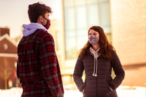 Two masked students talk to each other in the sunshine.