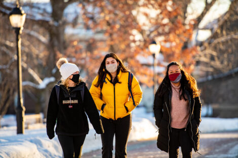 Three masked students walk