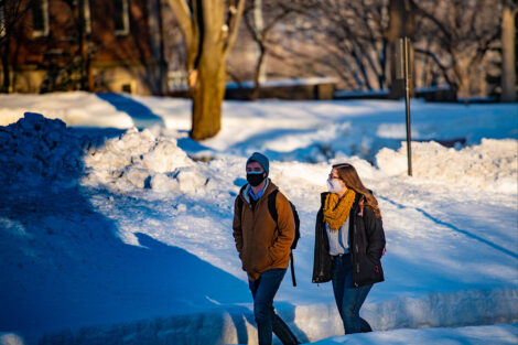 Two masked students walk, surrounded by snow.