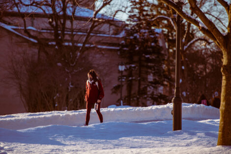 A masked student walks, surrounded by snow.