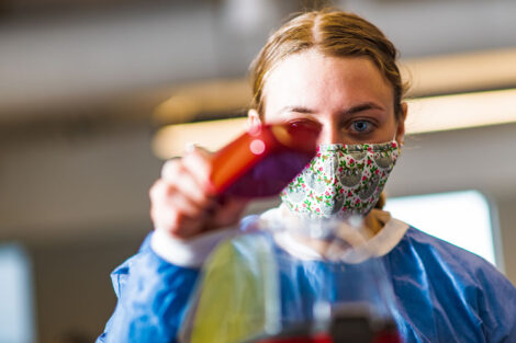 a student in a mask in a biology lab in Rockwell measures popcorn