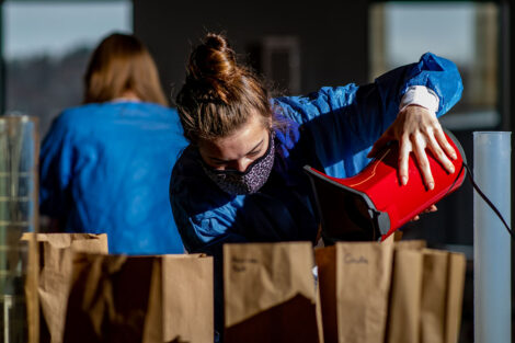 a student in a mask pours popcorn into paper brown bags