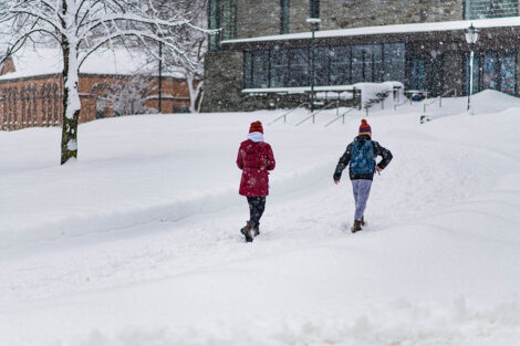 Two students walk away from the camera, toward Skillman Library, surrounded by snow