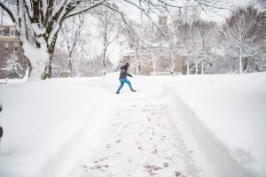 A student crosses a snow-covered path in the Quad