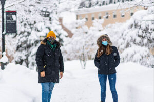 Two masked students stand socially distant, surrounded by snow on the ground and trees.