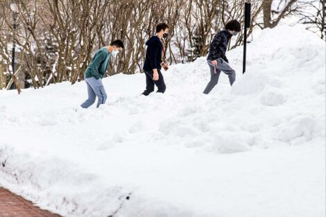 Three masked students walk up a path, surrounded by snow.