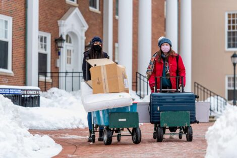 Two masked individuals roll storage containers past residence halls