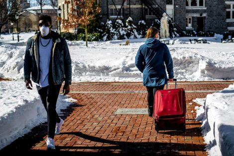 Two masked students pass each other, distanced. One rolls a red suitcase behind them.