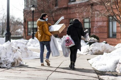 Two masked students carry bags.
