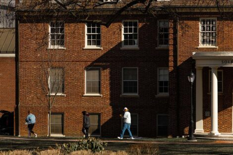 A masked student walks in front of a residence hall.
