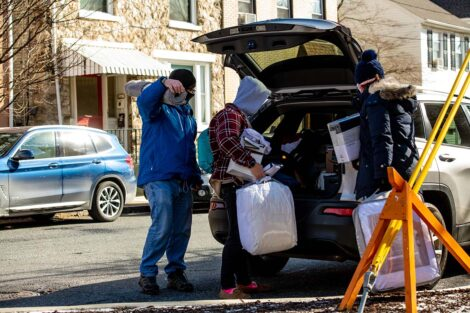 A student and their family, masked, picks up storage containers out of the trunk of their vehicle.