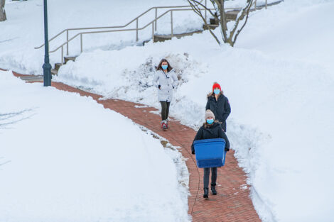 Three masked individuals walk down a sidewalk, surrounded by snow. One individual carries a storage box.