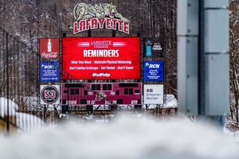The scoreboard at Fisher Field illuminates with Important Reminders: wear your mask, stay distanced, get tested.