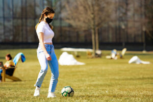 A masked student kicks a soccer ball on the Quad. Skillman Library is behind them.