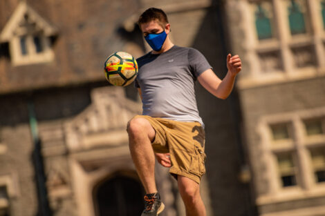 A masked student kicks a soccer ball with Hogg Hall behind them.