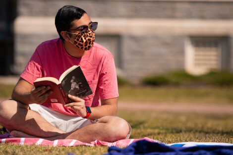 A masked student holds open a book, sitting on a blanket on the grass of the Quad.