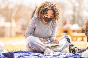 A masked student reads a book, sitting on a blanket on the Quad.