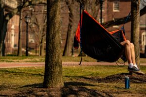 A student's legs hang out of a hammock on the Quad.