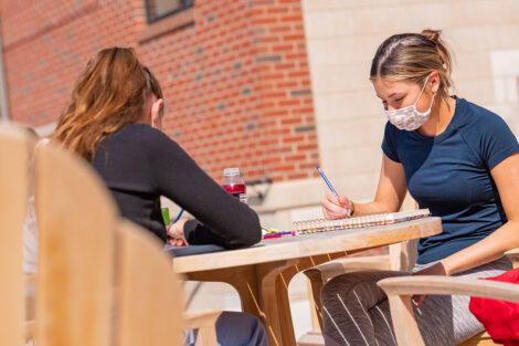 Two masked students sit opposit of each other at a table outside of a brick building.