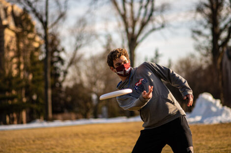 A masked student throws a frisbee on the Quad outside of Pardee Hall