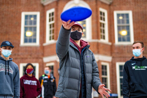 A student wearing a mask tosses a frisbee with other students standing behind them.