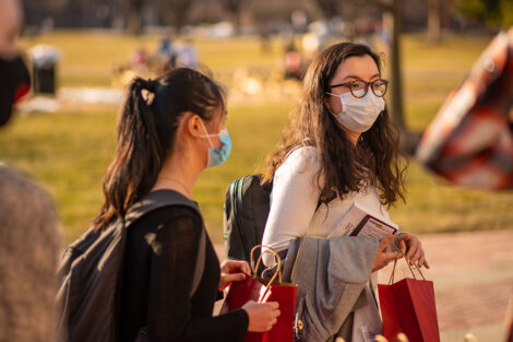 Two masked students carry red paper bags on the Quad.