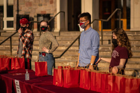 Four masked students stand behind a table, covered in a red table cloth. Red paper bags are on top of the table.