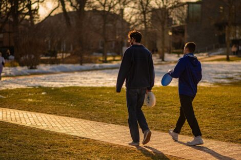Two students walk down a path, holding frisbees.