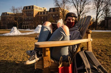 A masked student sits in an Adirondack chair with knees up, on the Quad in front of Pardee Hall.