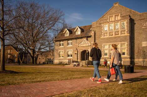 Two students walk on a path in front of Hogg Hall.
